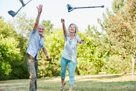 crutch: Senior couple in the park playfully throws crutches in the air