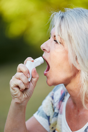 breathlessness: Senior woman using spray as a medicine against Asthma