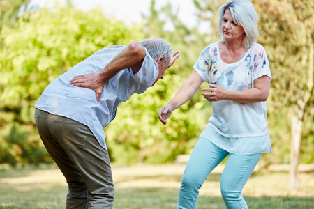hand on hip: Senior woman helps man having lumbago pain in the park in summer Stock Photo