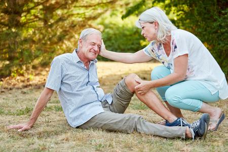 Frau gibt Erste-Hilfe zu einem Mann mit einer Knieverletzung und tröstet ihn