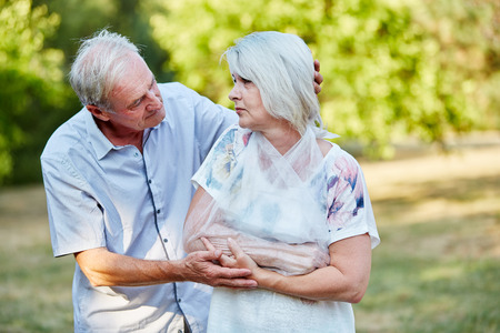 swelling: Man comforting old woman with broken arm in a loop