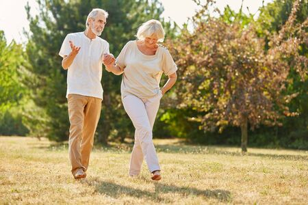 Couple in love holding hands on a walk in the park in summer