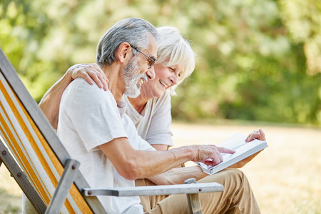 Happy seniors reading a book together in the nature in summer Stock Photo