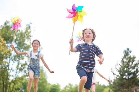 Kids with pinwheels playing at the park