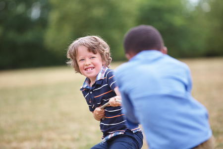 pulling rope: Two boys at a tug of war at the park