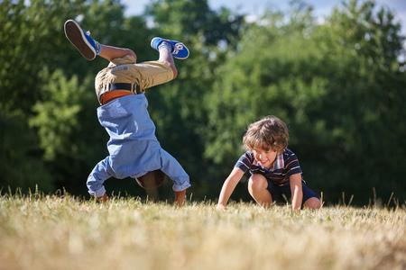 Deux enfants faisant un saut périlleux et souriant dans la nature