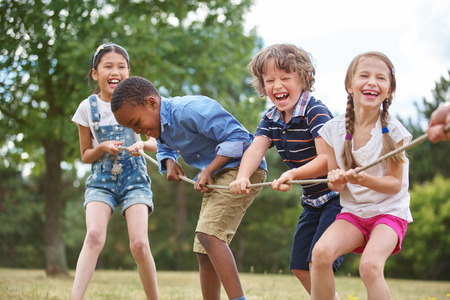Children playing tug of war at the park Stock Photo
