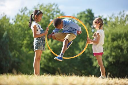 Boy jumps through hula hoop at the park Stock fotó