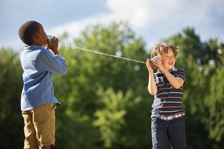 communication: Deux garçons jouent étain peut téléphoner à l'autre dans le parc Banque d'images