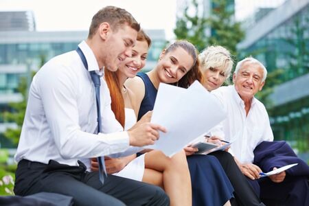 team working: Business people in summer working together on a contract outdoors Stock Photo