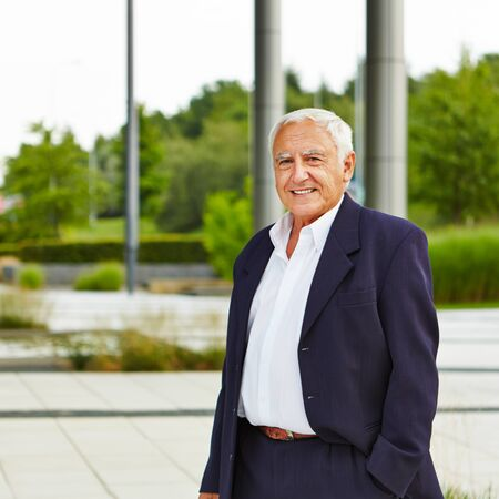smiling businessman: Retired old businessman standing smiling outdoors Stock Photo