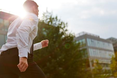 Actieve business man loopt in de stad in de zomer met achterlicht Stockfoto