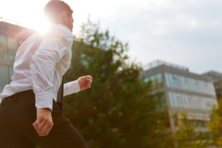 Active business man running in city in summer with back light