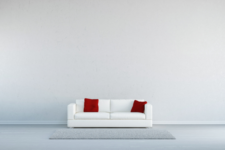 Couch with pillows and a carpet in front of a concrete wall Foto de archivo