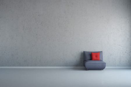 Grey chair with red cusion in front of concrete wall with copy space