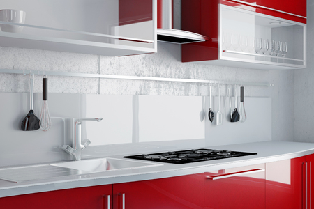 red kitchen: New red kitchen with sink and stove on a wall Stock Photo