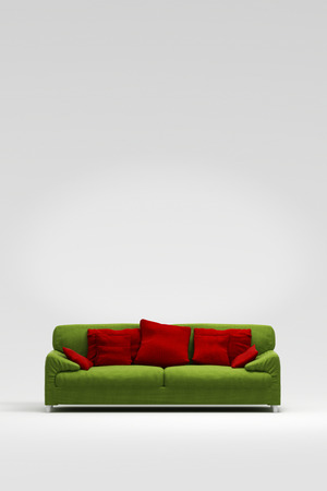 red pillows: Green sofa with red pillows in front of a white wall Stock Photo