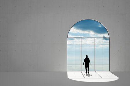 silhouette maison: L'homme dans le grenier regarde par la fenêtre au ciel avec des nuages