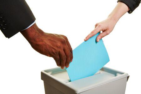Handen die stembiljet tijdens de verkiezingen over een stembus