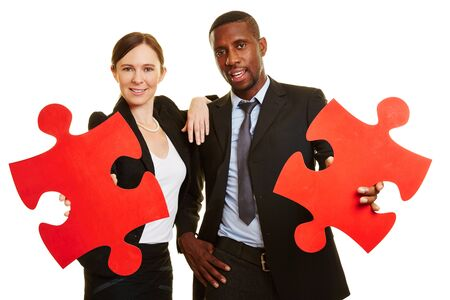 Smiling business people holding two red jigsaw puzzle pieces 版權商用圖片