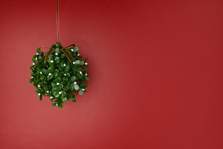 muerdago: Muérdago corona de flores colgando de navidad delante de una pared roja (3D)