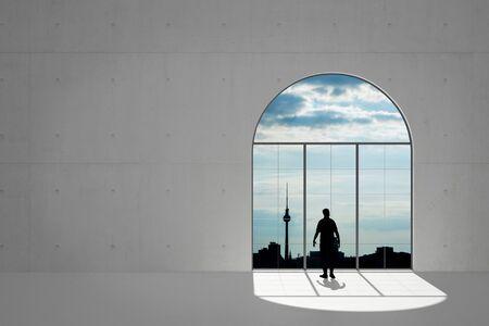 Man in een betonnen zolder met uitzicht op de wind in de Berlijnse stad Stockfoto