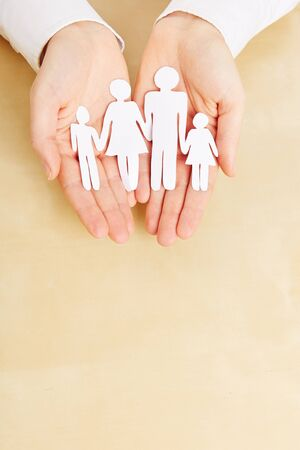 family units: Two female hands holding a paper family sillhouette Stock Photo