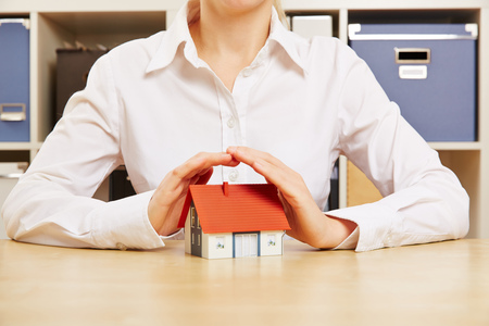 household insurance: Hands of a business woman as roof protecting a small house
