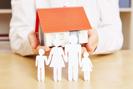 household insurance: Paper family with kids and a house in the hands of a woman Stock Photo