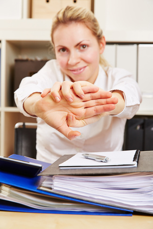 woman stretching: Young business woman in office at her desk stretching her arms to the front