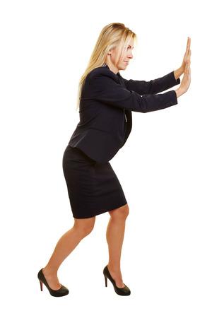 pantomima: Mujer de negocios rubia empujando con fuerza una pared imaginaria hacia el lado