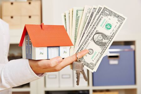 household insurance: Hand of a woman holding small house with keys and Dollar money bills Stock Photo