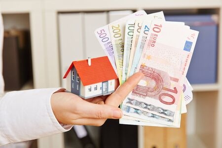 household insurance: Hand holding house and Euro money as concept for real estate financing Stock Photo