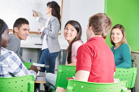 high class: Happy high school students at math class chatting Stock Photo