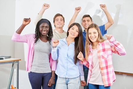 clench: Group of students clench their fists and raise their arms out of joy