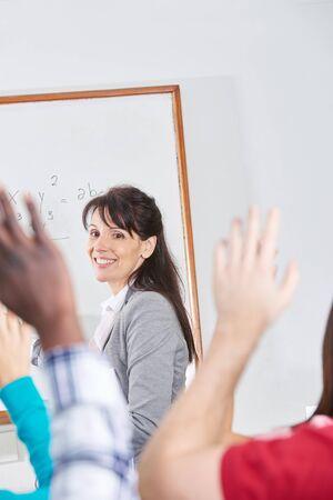 school teens: Teacher giving a class and students raising their hands