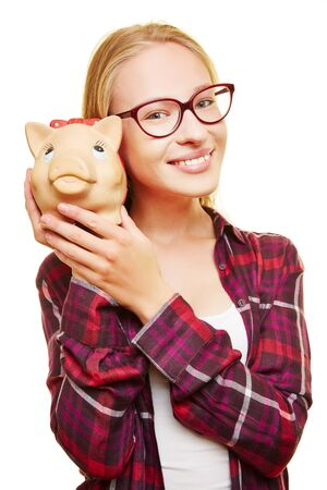 thrift box: Smiling female teenager with glasses and a piggy bank in her hands