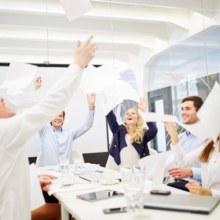 throw paper: Business people celebrates their success and throws sheets of paper in the air during a business meeting Stock Photo