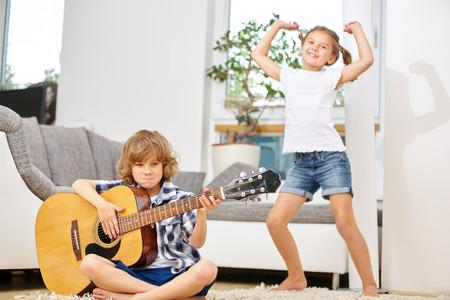 Muchacho que juega música con la guitarra y la niña feliz bailando en casa