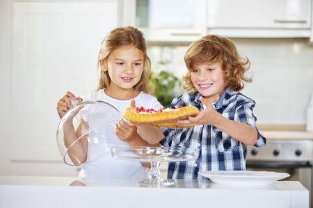 fruitcake: Children presenting their homemade fruitcake in the kitchen