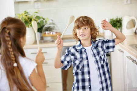 sibling rivalry: Two children fighting in fun with wooden spoons in the kitchen