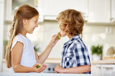 daring: Girl daring boy to lick on a lime fruit in the kitchen