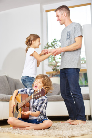 boy playing guitar: Boy playing guitar and father and sister dancing to the music at home
