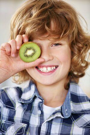 nonsense: Smiling boy holding kiwi half in front of his eye Stock Photo