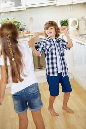sibling rivalry: Two kids fighting with wooden spoons in fun in a kitchen