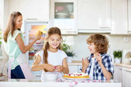 prepare: Two happy kids baking a fruit cake with red currants in the kitchen Stock Photo