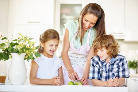 citrus family: Mother and children cutting lime fruits in the kitchen