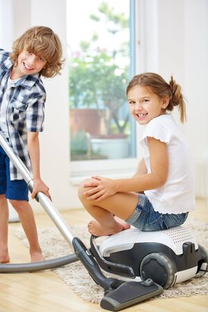 child boy: Two siblings cleaning at home with vacuum cleaner Stock Photo