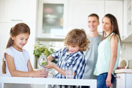 vasos de agua: Dos ni�os que beben agua con cal fresca en la cocina mientras los padres est�n viendo