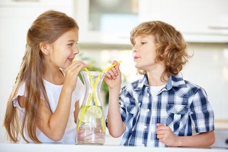 Dwoje dzieci do picia świeżą wodę ze słomą w kuchni Zdjęcie Seryjne